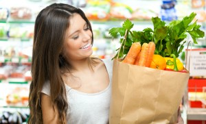 Woman holding a shopping bag full of vegetables